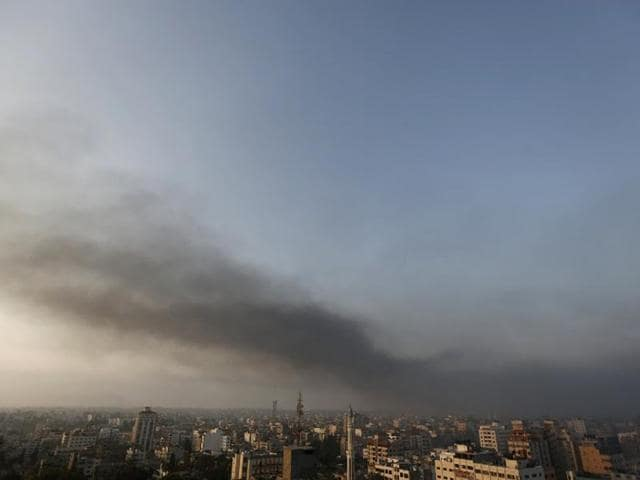 Smoke from Israeli strikes rises over Gaza City early as the sun rises on July 29, 2014. The overnight strikes came after a day of heavy Hamas-Israeli fighting in which nine children were killed by a strike on a Gaza park where they were playing. (AFP/Mohammed Abed)