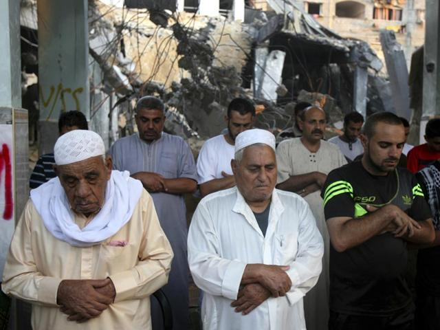 Palestinians participate in early morning prayer during the first day of Eid al-Fitr inside the destroyed Al Farouk mosque which was destroyed by an overnight Israeli strike in Rafah on July 29, 2014. (AP Photo/Eyad Baba)