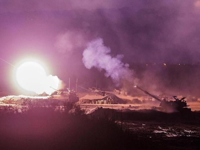 An Israeli artillery gun fires a 155mm shell towards targets in the Gaza Strip from their position near Israel
