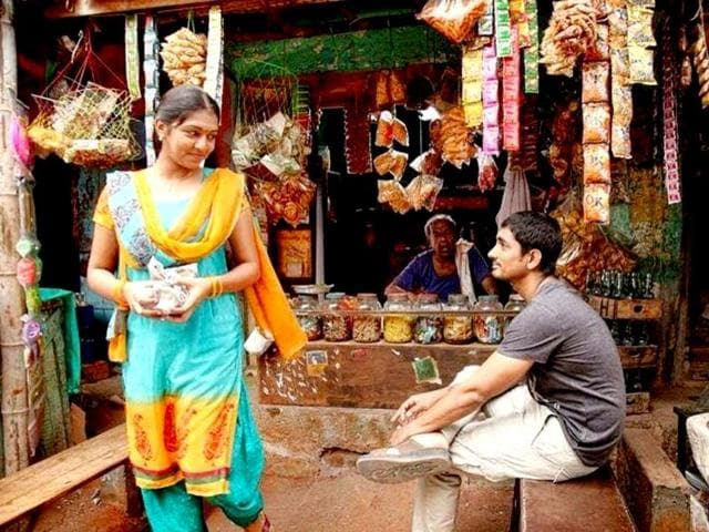 The film is a love triangle between an aspiring filmmaker (Siddharth), an idli seller (Lakshmi Menon) and a dangerous gangster (Simhaa) and set in the temple town of Madurai. (jigarthanda/Facebook)