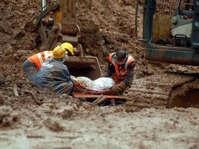 NDRF personnel with a body of a victim of landslide at Malin village on Thursday. (PTI Photo)