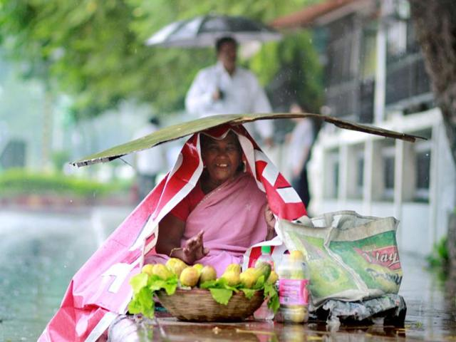 A-woman-protects-herself-during-rain-at-Mandi-House-in-New-Delhi-Arun-Sharma-HT-photo