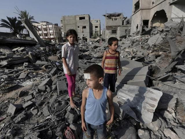 Palestinian-Seraj-Ismail-Abdel-Al-5-lightly-wounded-in-an-overnight-Israeli-strike-inspects-the-damage-to-several-buildings-in-Gaza-City-northern-Gaza-Strip-AP-photo