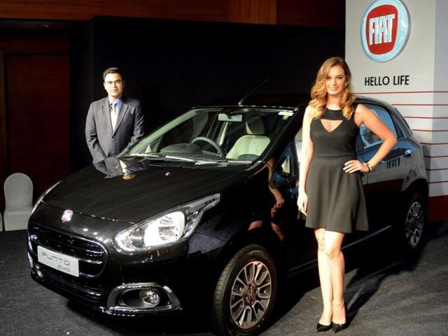 Indian-Fiat-Chrysler-President-and-Managing-Director-Nagesh-Basavanhalli-L-and-Indian-German-actress-and-model-Evelyn-Sharma-pose-in-front-of-Fiat-Punto-Evo-car-during--a-launch-in-New-Delhi-on-August-5-2014-Fiat-has-launched-a-new-Punto-Evo-targetting-the-Indian-market--Photo-AFP