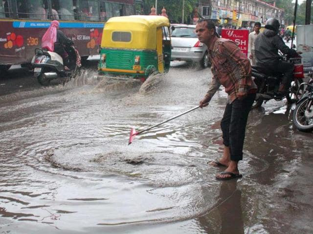 A-man-struggles-to-remove-the-water-that-accumulated-in-front-of-his-shop-in-Indore-on-Tuesday-Arun-Mondhe-HT-photo