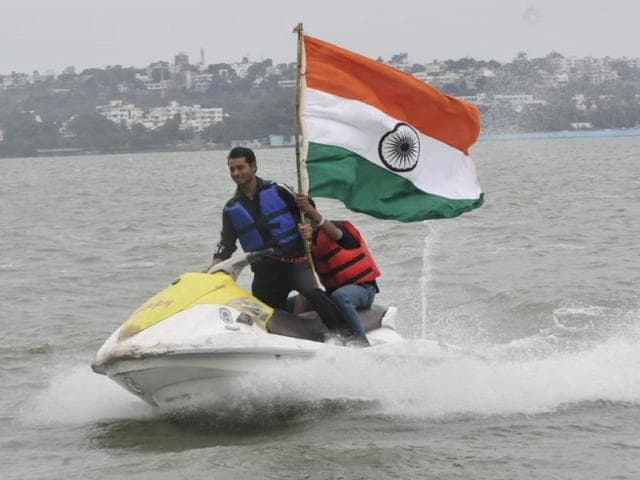 Youngsters enjoy water scooter ride with the national flag on the eve of Independence Day in Bhopal. (Mujeeb Faruqui/HT photo)