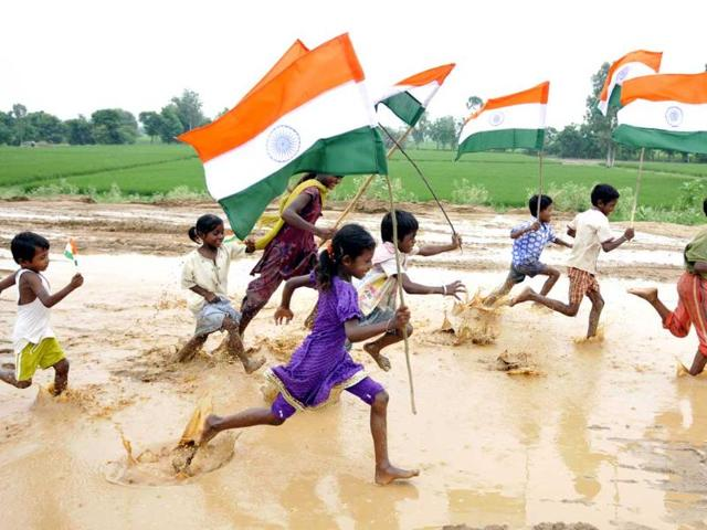 Children play with the national flag on the eve of Independence day near Ramgarh village, Patiala. (Bharat Bhushan/HT Photo)
