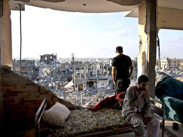 Hamad-R-and-Mohammed-L-sit-in-a-destroyed-apartment-building-where-they-lived-with-their-families-in-the-neighborhood-of-Al-Shaas-in-the-north-of-the-Gaza-Strip-enclave-AFP-Photo