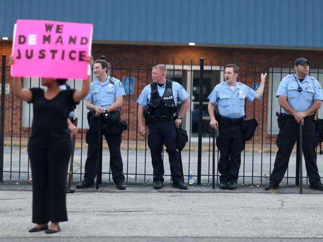 "A demonstrator holds a sign reading, ""We Demand Justice"", in front of a line of police as demonstrators continue to make their voices heard in the shooting death of Michael Brown. (AFP Photo)"