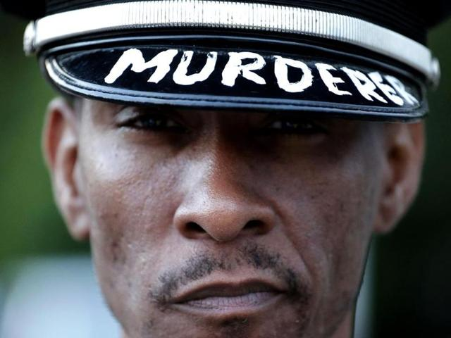 A man wearing a police hat protests Sunday for Michael Brown, who was killed by a police officer last Saturday in Ferguson, Mo. (AP Photo)