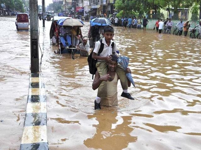 A man carries his child, wades through a waterlogged road after a heavy downpour at Chandmari in Guwahati. (PTI Photo)