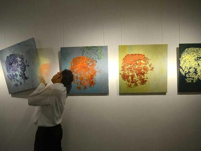 A-gallery-official-adjusts-a-painting-incorporating-footprints-of-an-elephant-by-Singapore-based-artist-Alpana-Ahuja-at-the-Ganapati-to-Gajah-art-exhibition-in-New-Delhi-AFP