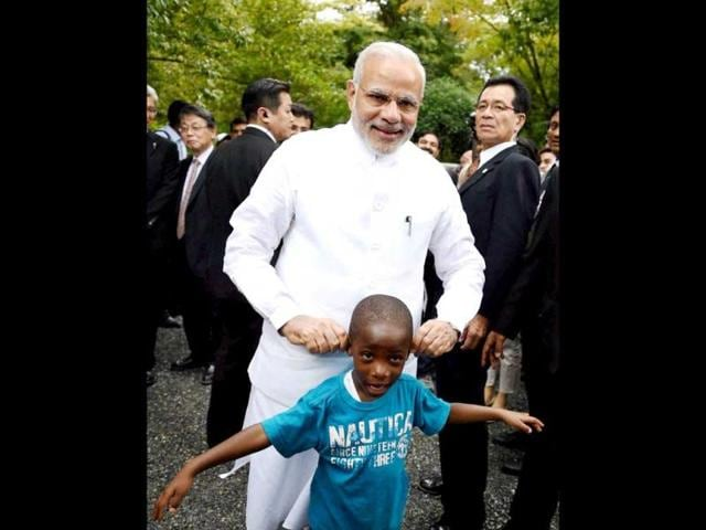 PM Modi shares a light moment with a child during his visit at Golden Pavilion, Buddhist temple in Kyoto. (PTI Photo)