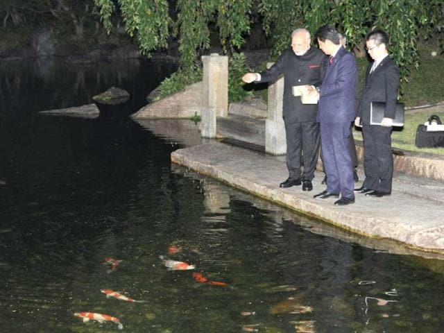 PM Narendra Modi (L) and Japanese Prime Minister Shinzo Abe (C) feed fish at the State Guest House in Kyoto. (AFP Photo)