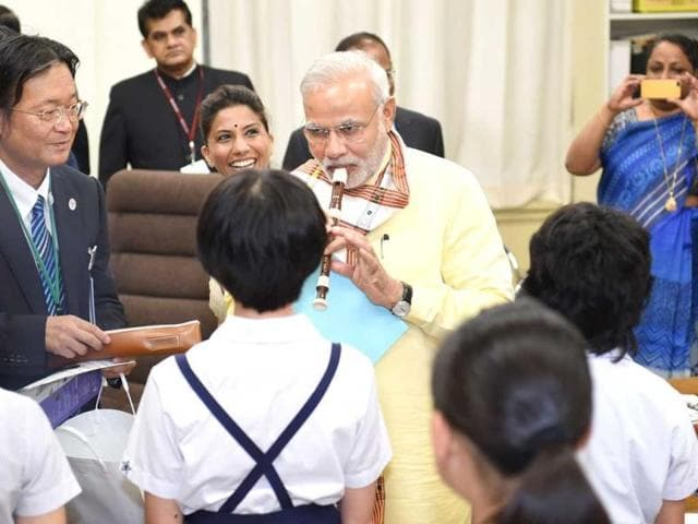 PM Modi plays a flute as he visits a music class in an elementary school in Tokyo. (AFP Photo)