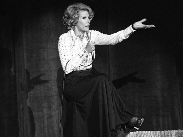 In this August. 13, 1975 photo, comedian Joan Rivers performs at the MGM in Las Vegas. The raucous, acid-tongued comedian who crashed the male-dominated realm of late-night talk shows and turned Hollywood red carpets into danger zones for badly dressed celebrities, died Thursday. (AP)