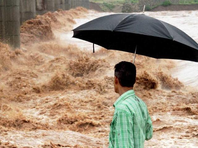 A man holding umbrella looks on as Tawi river rages dangerously during heavy rains in Jammu. (PTI Photo)