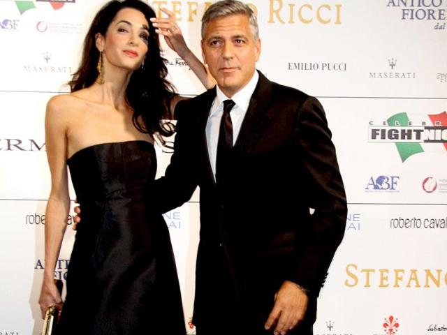 A-dapper-as-ever-George-Clooney-was-spotted-with-his-much-too-caked-up-fiance-Amal-Alamuddin-at-a-charity-gala-Celebrity-Fight-Night-in-Florence-Here-he-let-the-cat-out-of-the-bag-and-said-that-he-will-marry-her-sometime-within-the-next-two-weeks-in-Venice-Photo-courtesy-AFP