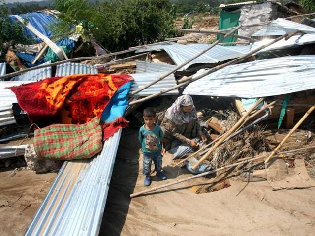 A lady along with her child salvages usable items from her destroyed house after flash floods hit Majheen village about 20 km from Jammu. (HT Photo/Nitin Kanotra)