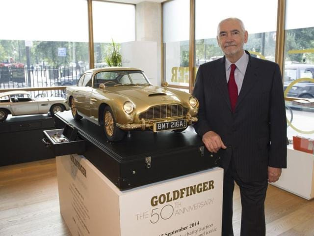 Michael-G-Wilson-Producer-EON-Productions-poses-with-the-unique-gold-Aston-Martin-DB5-Photo-AFP