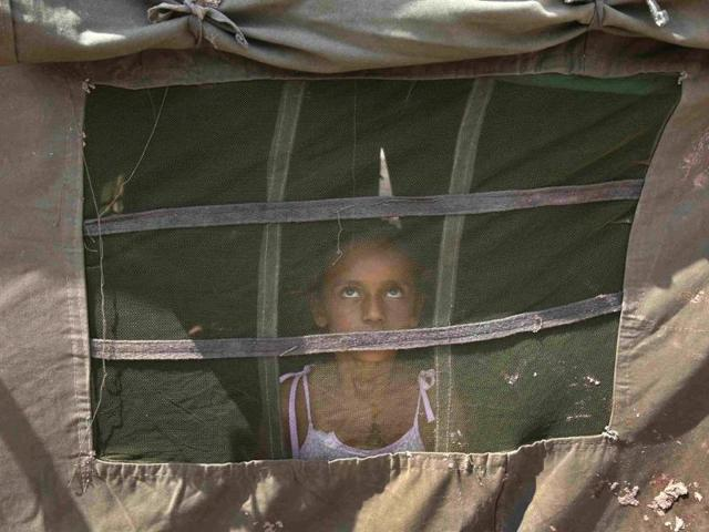 A-girl-from-a-flood-affected-area-watches-a-military-chopper-not-pictured-from-inside-an-Indian-Army-tent-at-a-relief-camp-on-the-outskirts-of-Jammu-Reuters-Photo