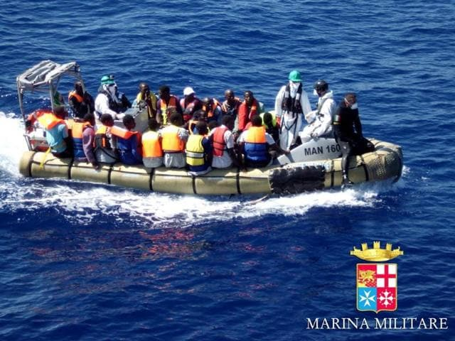 In-this-handout-picture-released-by-the-Italian-Navy-migrants-sit-in-a-boat-during-a-rescue-operation-off-the-coast-of-Sicily-AFP-photo-Marina-Militare