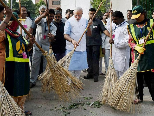 Narendra-Modi-wields-a-broom-with-NDMC-workers-to-launch-Swachh-Bharat-Abhiyan-in-Valmiki-Basti-in-New-Delhi-PTI-Photo