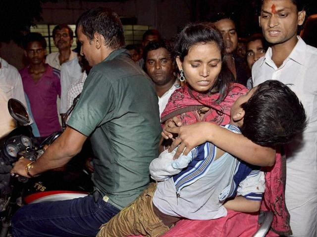 A woman takes an injured kid to hospital after a stampede during Dussehra celebrations at Gandhi Maidan in Patna on Friday. PTI
