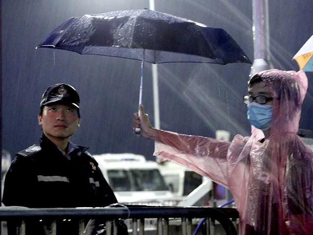 A young pro-democracy demonstrator holds an umbrella for a police officer during a demonstration in Hong Kong. (AP Photo)