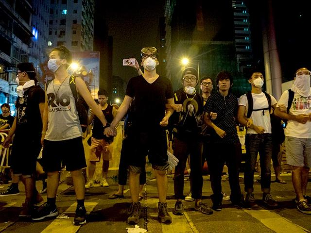 Pro-democracy demonstrators link arms and guard their protest camp in Mongkok, Hong Kong. (AFP Photo/ Jerome Taylor)