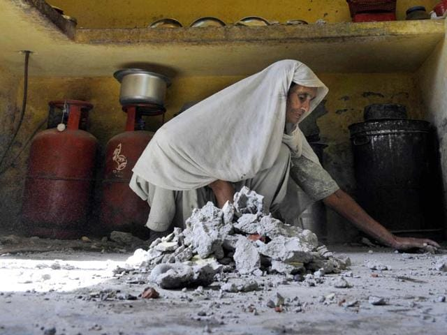 A-lady-clears-her-damaged-house-after-heavy-firing-from-the-Pakistan-side-of-the-border-at-Kanachak-village-in-Jammu-Nitin-Kanotra-HT-Photo