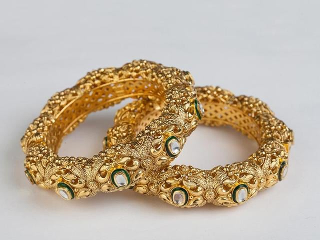 An-intricately-carved-set-of-gold-and-kundan-bangles-with-stone-detailing-and-green-accents-From-Diamond-Polki-by-SSJ-Karol-Bagh-Price-Rs-3-85-lakh