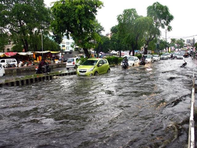 Commuters-wade-through-a-waterlogged-road-near-Jyoti-Talkies-in-Bhopal-on-Saturday-after-heavy-rain-lashed-the-city-Praveen-Bajpai-HT-photo