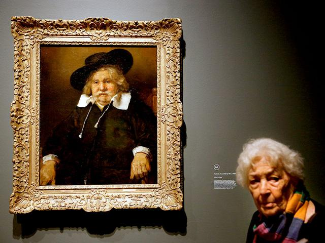 A-visitor-walks-past-a-painting-entitled-Portrait-of-an-Alderly-Man-by-Dutch-artist-Rembrandt-Photo-AFP