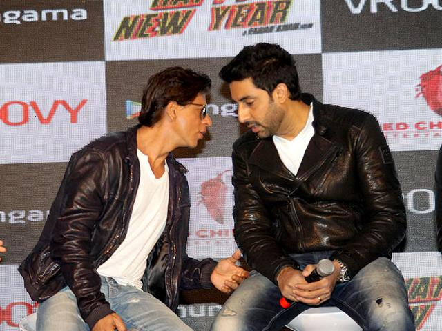 Shah Rukh Khan and Abhishek Bachchan caught in a candid moment sharing a secret at an event to promote the official mobile game of Happy New Year. (Photo: IANS)