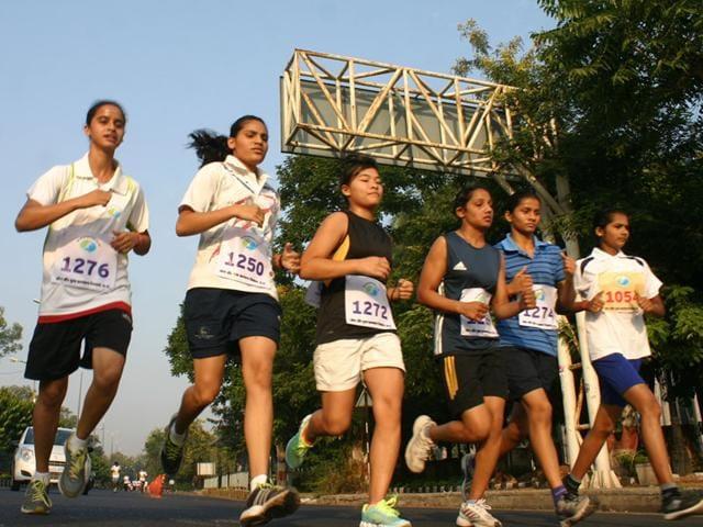 Girls take part in a mini marathon during Madhya Pradesh Foundation Day celebrations in Bhopal. (HT photo)