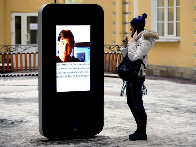 A-woman-stands-next-to-a-screen-showing-a-portrait-of-Steve-Jobs-on-a-memorial-to-late-Apple-Corp-co-founder-in-the-courtyard-of-the-Techno-Park-of-the-St-Petersburg-National-Research-University-of-Information-Technologies-Mechanics-and-Optics-in-St-Petersburg-Russia-AP-Photo