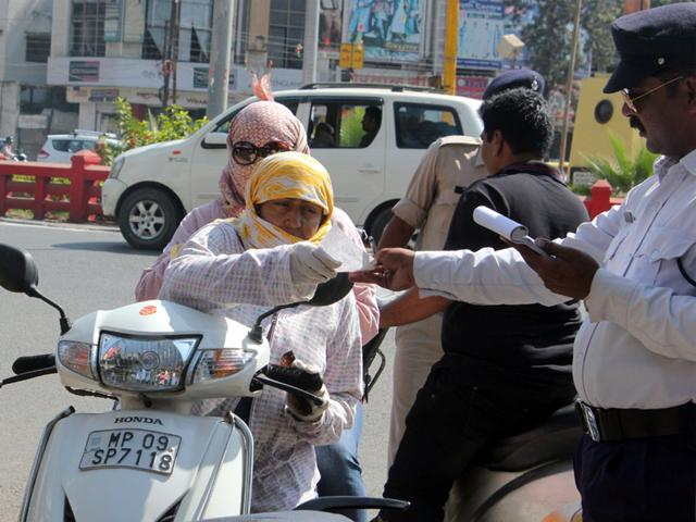 A-woman-being-served-challan-for-not-wearing-helmet-during-a-checking-drive-in-Indore-on-Thursday-Shankar-Mourya-HT-photo