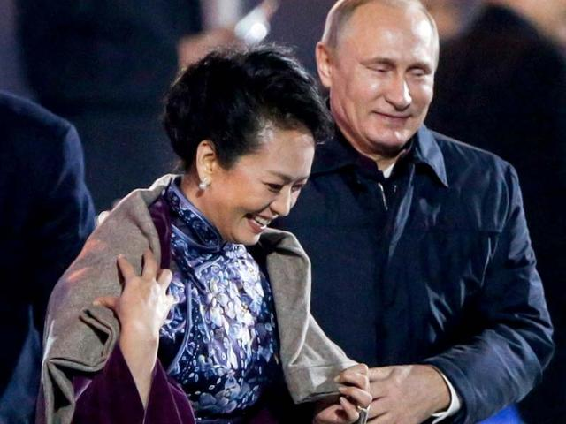 Russia-s-President-Vladimir-Putin-right-helps-put-a-blanket-on-Peng-Liyuan-the-wife-of-China-s-President-Xi-Jinping-as-they-watch-a-lights-and-fireworks-show-to-celebrate-the-Asia-Pacific-Economic-Cooperation-APEC-Leaders-Meeting-in-Beijing-Reuters