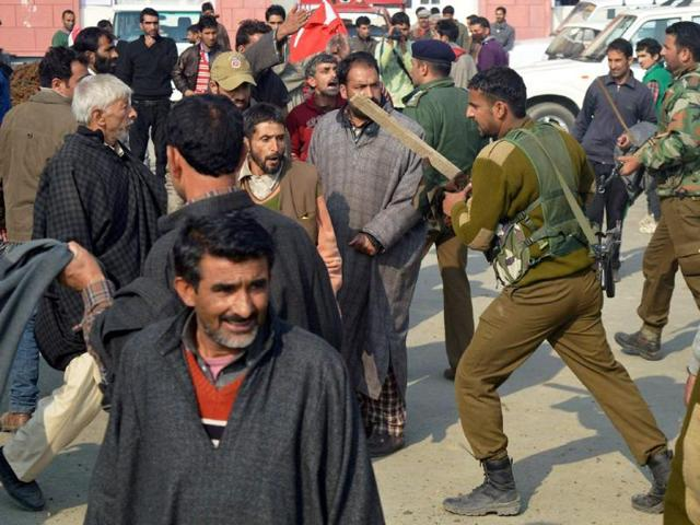 Policeman-dispersing-two-warring-group-of-supporters-of-National-Conference-and-Peoples-Democratic-Party-during-election-rallies-in-South-Kashmir-s-Kulgam-district-on-Thursday-PTI-Photo