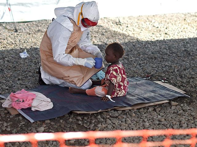 A-health-official-dressed-in-protective-gear-examines-children-suffering-from-the-Ebola-virus-at-Makeni-Arab-Holding-Centre-in-Makeni-Sierra-Leone-AP-Photo-Tanya-Bindra