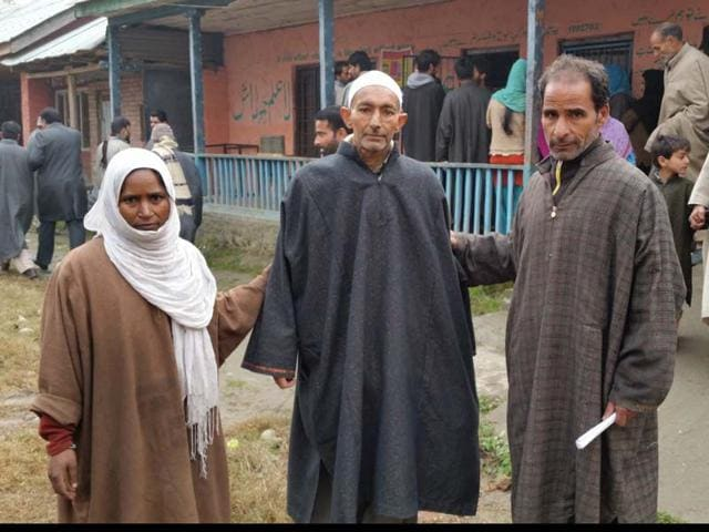 Cancer-patient-Ghulam-Nabi-Khanday-centre-accompanied-by-wife-and-elder-brother-at-the-Shadipora-polling-station-in-Sonawari-constituency-on-Tuesday-HT-Photo
