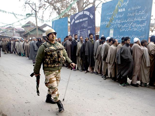 Paramilitary soldiers walks past Kashmiri voters standing in queue outside a polling station during the first phase of voting to the Jammu and Kashmir state assembly elections in Lar, some 30 kilometers (19 miles) north of Srinagar. (AP photo)
