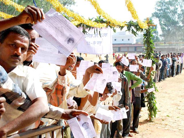 Voters display their voter identity cards, as they wait to cast their votes at a polling station during the first phase of Jharkhand assembly election, in Latehar. (PTI photo)
