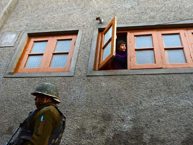A Kashmiri child looks out from the window of a residence as Indian paramilitary personnel gather near the scene of a gunfight with militants on the outskirts of Srinagar. (AFP Photo)