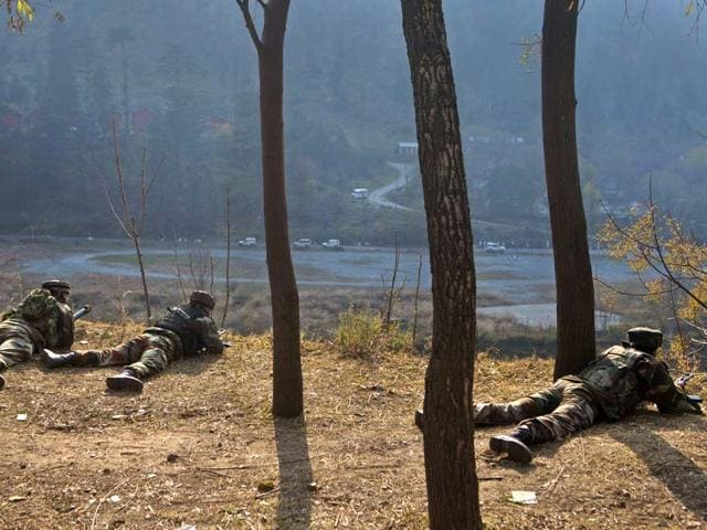Soldiers take position on a road overlooking an army barrack during a gun battle with militants in Gingal, some 90 kilometers (56 miles) north of Srinagar. (AP Photo)