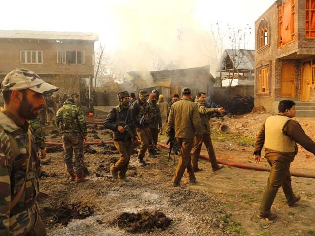 Policemen inspect the site of a gun battle on the outskirts of Srinagar. (AP Photo)