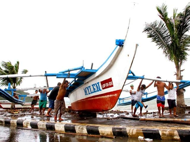 Fishermen-carry-thier-outrigger-to-higher-ground-in-Legazpi-City-south-of-Manila-ahead-of-the-landfall-of-Typhoon-Hagupit-AFP-Photo