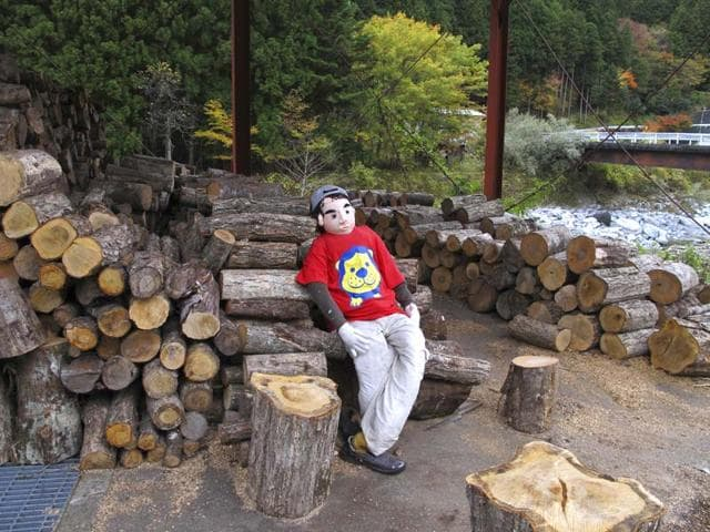 A-teenager-look-alike-scarecrow-sits-on-a-log-pile-in-Nagoro-Tokushima-Prefecture-southern-Japan-AP-photo
