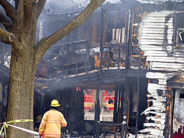 A-firefighter-stands-outside-a-smoldering-house-where-a-small-plane-crashed-in-Gaithersburg-Maryland-AP-Photo